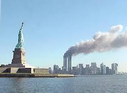 A Estátua da Liberdade com as Torres Gémeas do WTC ao fundo, após terem sido atingidas