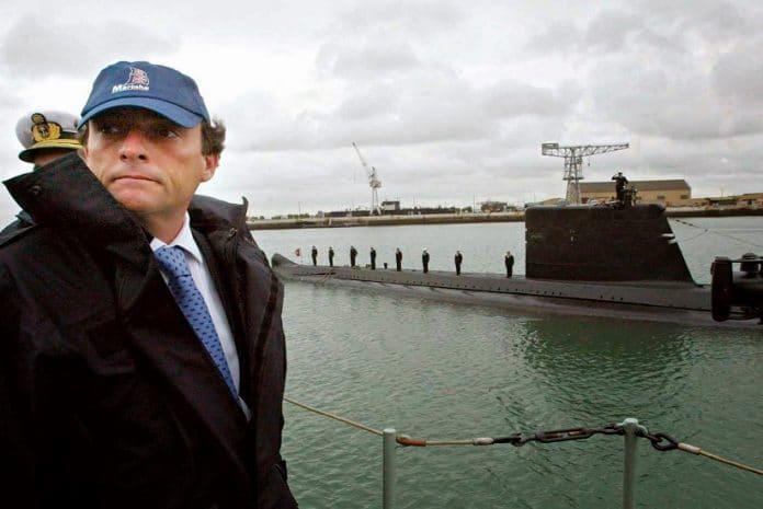 O Ministro da Defesa Nacional com um chapéu da marinha durante a viagem de lancha que o levou à Base Naval do Alfeite, para a cerimónia de assinatura. Ao fundo um submarino